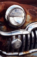Color photograph of the chrome grill and rust of an antique DeSoto antique automobile