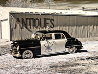 Black and White Infrared photograph of an old police car in front of an Antique building by Crystal Nederman.