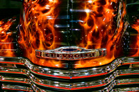 Color photograph of the hood of a Chevrolet set afire with flames