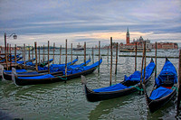 Rows of gondolas with the bright blue covers front San Giorgia Maggiore in Venice, Italy by Crystal Nederman