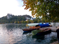 Photograph of the Pletna boats with the Bled Castle on the cliffs overlooking the lake