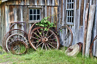Color photograph of wagon wheels leaning against a weathered barn by Crystal Nederman