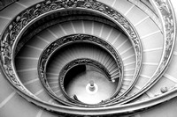 This is a black and white photograph of the ornate stairway at the Vatican Museum.